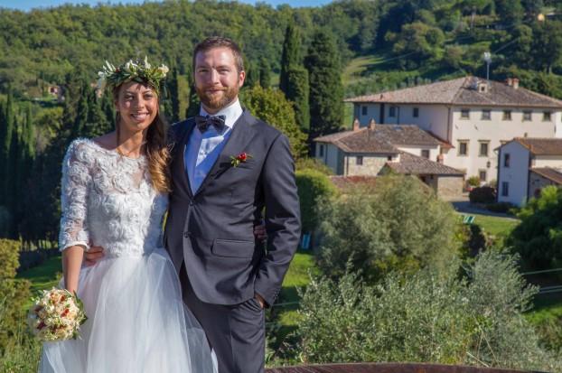 Una coppia di novelli sposi in primo piano e una Villa per Matrimoni in Toscana alle loro spalle, Villa Campestri.